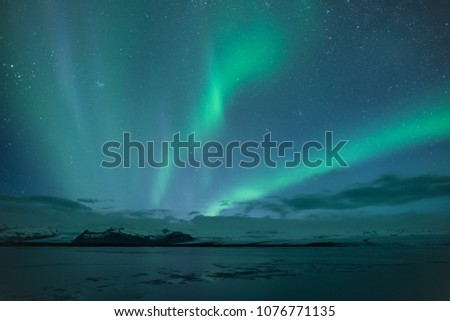 Northern lights aka Aurora Borealis glowing on sky in Jokulsarlon glacier lagoon with snow capped mountains in background at night in Iceland #1076771135
