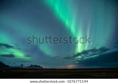 Northern lights aka Aurora Borealis glowing on sky in Jokulsarlon glacier lagoon with snow capped mountains in background at night in Iceland #1076771144