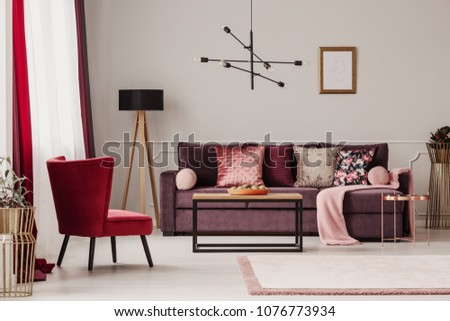 Red armchair near wooden table and purple sofa against the wall with mockup in living room interior #1076773934