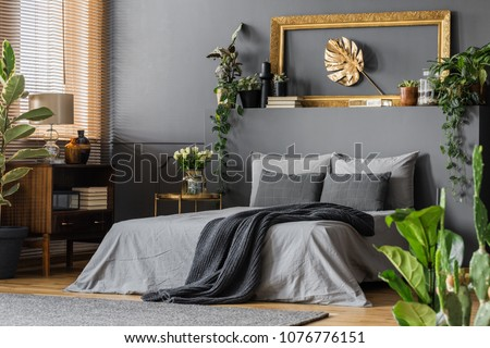 Gold leaf in frame on the wall above grey bed with dark blanket in elegant bedroom interior #1076776151