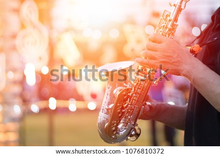 International Jazz day background concept. Saxophone, music instrument played by saxophonist player musician in festival Royalty-Free Stock Photo #1076810372
