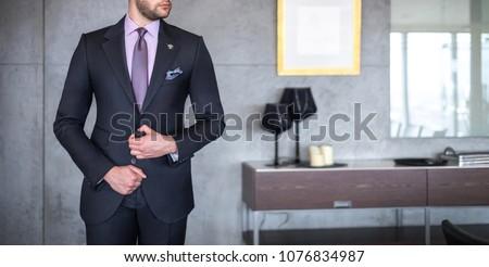 Man in custom tailored business suit posing indoors #1076834987
