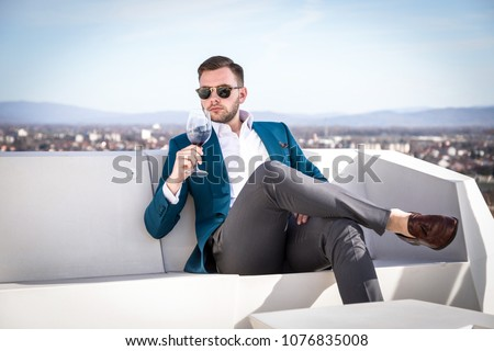 Man millionaire in expensive custom tailored suit, sitting outdoors with glasses and holding a glass of red wine #1076835008