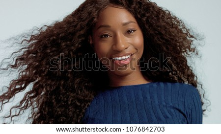 Beauty mixed race african american woman portrait in pink background with wind in hair on blue #1076842703
