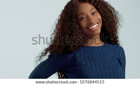 Beauty mixed race african american woman with hair blowed in air smiling at camera #1076844515