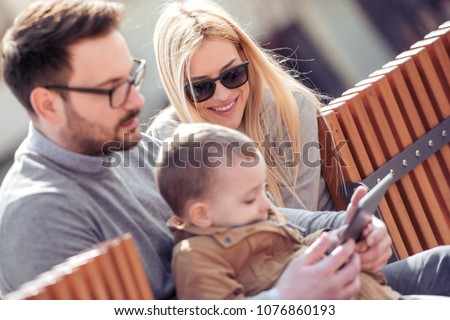Happy young family watching cartoon on tablet. #1076860193