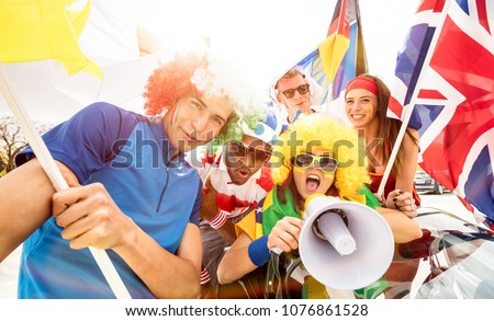 Football supporter fans friends cheering after soccer cup match hanging around with car and flags - Young people group with multicolored t-shirts having excited fun on sport world championship concept #1076861528