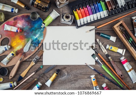 Set of artist accessories collection. Canvas, tube of oil paint, art brushes, palette knife lying on the wood table. Artist workshop background. Royalty-Free Stock Photo #1076869667
