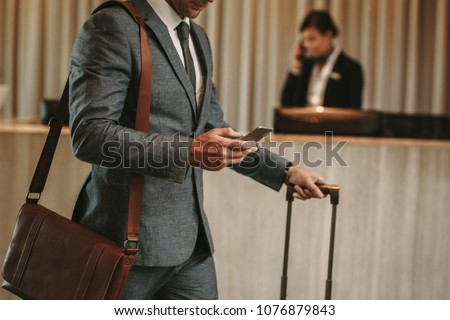 cropped shot of businessman in hotel lobby with mobile phone and luggage. Male business traveler arriving at his hotel, with focus on hands holding smart phone. #1076879843