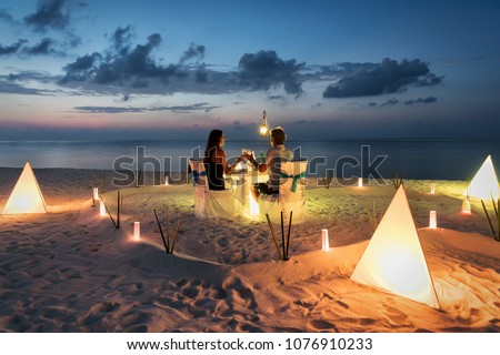 Honeymoon couple is having a private, romantic dinner at a tropical beach #1076910233