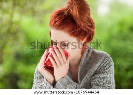 beautiful young woman with red hair sitting in the garden, relaxing, drinking coffee in a red coffee mug #1076944454