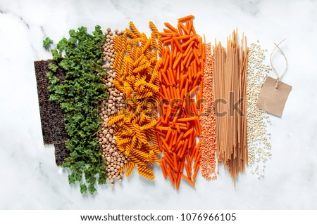 different types of gluten-free paste from chickpeas, red lentils, algae and healthy cereals on a white marble table. labels for writing text. shot from above. food background Royalty-Free Stock Photo #1076966105