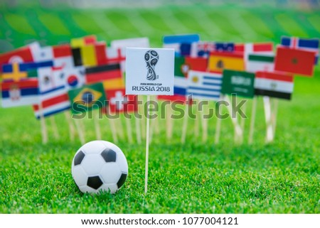 MOSCOW, RUSSIA - APRIL, 24, 2018: All nations flags and Official logo of FIFA World Cup 2018 in Russia. Flags on green grass, football stadium in background. #1077004121