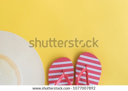 Summer hat and flip flops on a yellow background. Top view, flat lay #1077007892