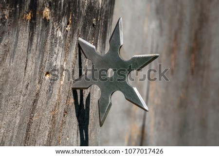 Shuriken (throwing star), traditional japanese ninja cold weapon stuck in wooden background #1077017426