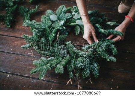 Woman making christmas wreath on a dark wooden table. Concept of florist's work before christmas holidays. #1077080669