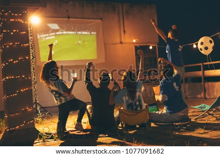 Group of young friends watching a football match on a building rooftop, drinking beer and cheering. Selective focus on the people in the middle #1077091682