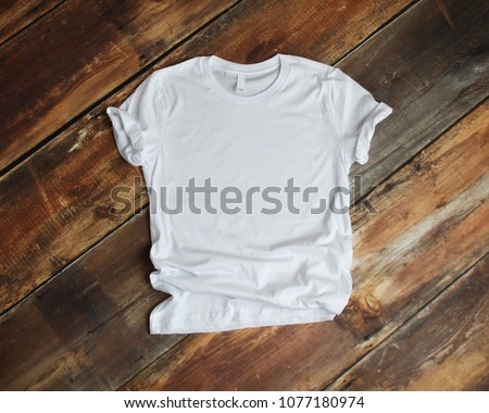 White T Shirt mockup flat lay on rustic brown wood background Royalty-Free Stock Photo #1077180974