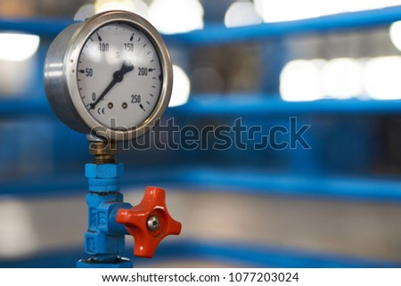 Close-up of a pressure gauge psi meter. Pressure meter and red faucet with steel blue pipe in natural gas treatment factory. #1077203024