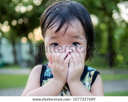 Cute asian little girl put his hand up cover mouth #1077327689