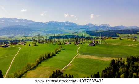 Panoramic view of idyllic mountain scenery in the Alps with fresh green meadows in bloom on a beautiful sunny day in springtime, Lucerne Switzerland #1077337433