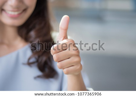successful girl pointing thumb up sign gesture; portrait of cheerful smiling woman pointing up approving, yes, ok, good, thumb up gesture; asian woman young adult model Royalty-Free Stock Photo #1077365906