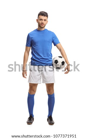 Full length portrait of a soccer player holding a football and looking at the camera isolated on white background #1077371951