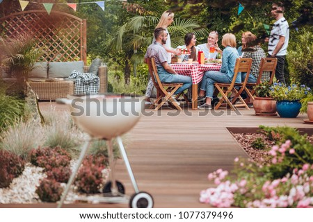 Wooden patio in the garden with a grill standing in the front and happy young people gathered around a table full of food during summer brake meeting #1077379496