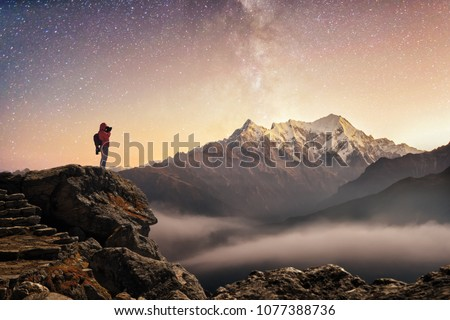 Photographer traveler who take picture of starry sky enjoying sunrise on peak of over snowy mountains in the Himalayas, Langtang, Nepal. Night colorful landscape. Starry sky with mountains at winter.