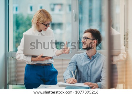 Manager giving feedback to young intern #1077395216