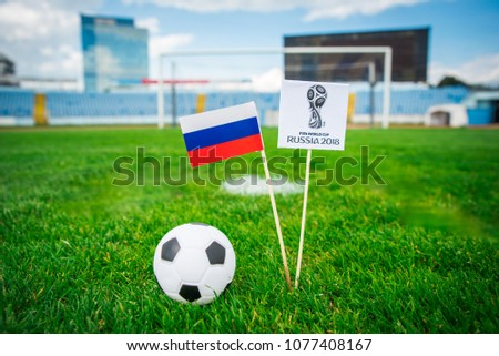 MOSCOW, RUSSIA - APRIL, 24, 2018: Official logo of FIFA World Cup 2018 in Russia and Russian national Flag. Green grass and football stadium in background. Edit space. #1077408167