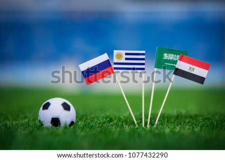 Group A draw in Football match. National Flags of Russia, Saudi Arabia, Egypt, Uruguay. Flags on green grass on football stadium #1077432290
