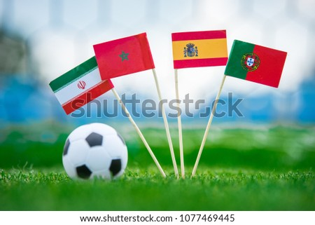 National Flags of Portugal, Spain, Morocco, IR Iran. Flags on green grass on football stadium. Group B draw. #1077469445
