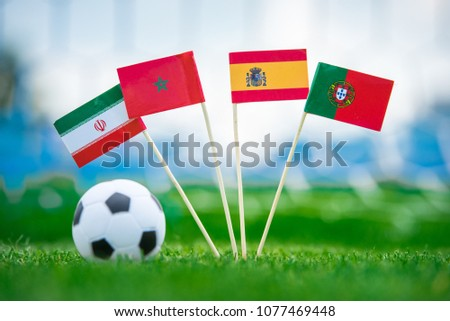 Group B National Flags of Portugal, Spain, Morocco, IR Iran. Flags on green grass on football stadium.  #1077469448