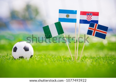 Group D - draw in football match. National Flags of Argentina, Iceland, Croatia, Nigeria. Flags on green grass on football stadium #1077493922