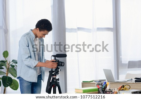 african american teenager setting camera for shooting video blog at home #1077512216