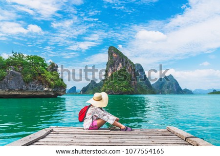 Traveler woman with backpack joy relaxing on floating wood bridge and looking Beautiful destination island, Panyee island, Phang nga bay, Travel Thailand, Natural landscape Asia, Summer vacation trip #1077554165