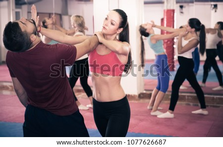 Sporty woman are training self-defense-karate with coach in gym. Royalty-Free Stock Photo #1077626687