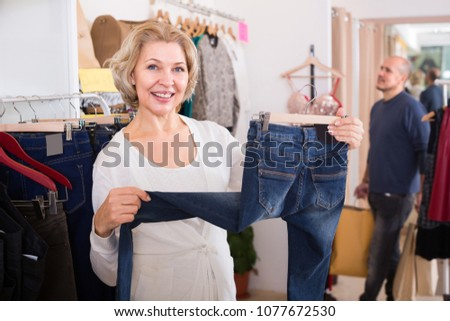Mature husband bored in clothing store and woman buying jeans  #1077672530