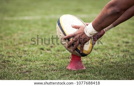 rugby player preparing to kick the oval ball during game #1077688418