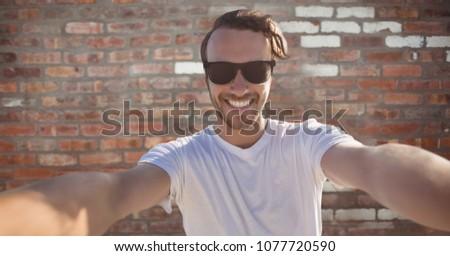 Man taking selfie against brick wall #1077720590