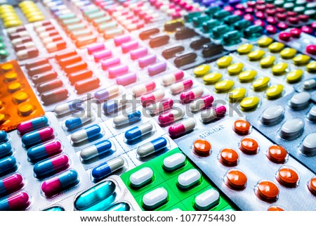 Colorful of tablets and capsules pill in blister packaging arranged with beautiful pattern with flare light. Pharmaceutical industry concept. Pharmacy drugstore. Antibiotic drug resistance. #1077754430