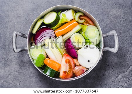 Vegetables stock or broth, vegetable soup top view in pot.