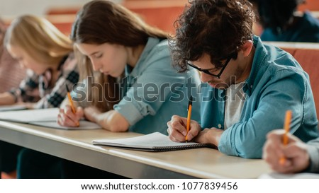 Row of Multi Ethnic Students in the Classroom Taking Exam/ Test/ Writing in Notebooks. Bright Young People Study at University. #1077839456