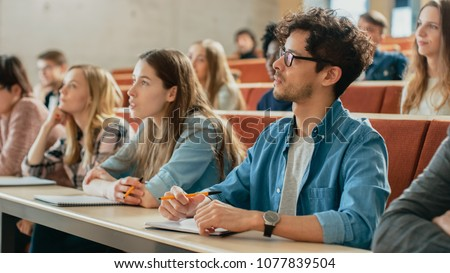 In the Classroom Multi Ethnic Students Listening to a Lecturer and Writing in Notebooks. Smart Young People Study at the College. Royalty-Free Stock Photo #1077839504