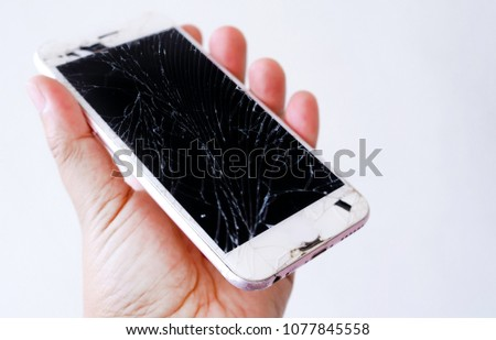 Hand hold the smartphone with broken screen isolated on white background