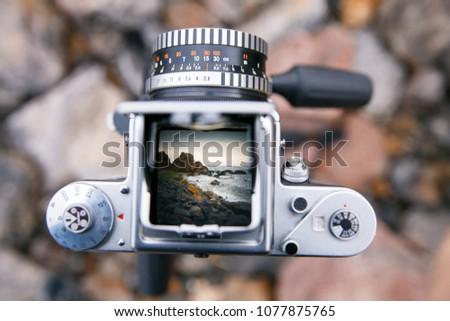 Looking at the viewfinder of medium format film camera