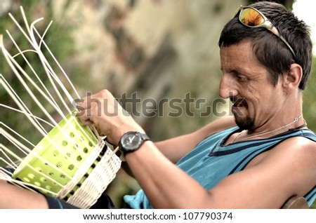 man manually weaving basket #107790374