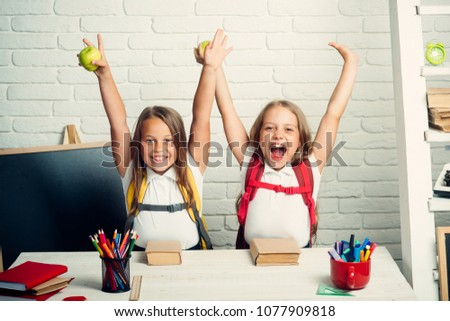 Back to school and home schooling. Happy school kids at lesson in september 1. Friendship of small sisters in classroom at knowledge day. Little girls eat apple at lunch break. School time of girls. #1077909818