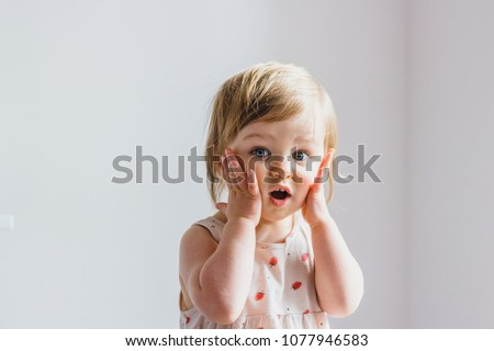 Surprised shocked child toddler girl with hands on her cheeks isolated on light background #1077946583